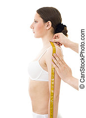 Measuring woman\'s shoulder length, with centimetre...