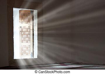 Light entering through open door to a dark empty room.