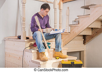 young handsome man sitting on floor holding clipboard with blueprint and pencil and looking on it