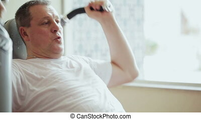 Working out on exercise machine - Mature man training on...