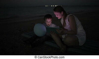 On the beach at night - Panning shot of a little boy and his...