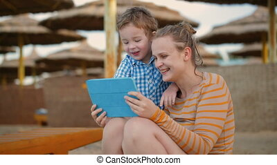 Little boy with is mother at a beach resort - Little boy...