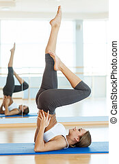 Woman exercising. Side view of beautiful young Indian woman training on yoga mat and smiling at camera