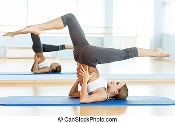 Women training on exercise mat. Side view of beautiful young woman training on yoga mat