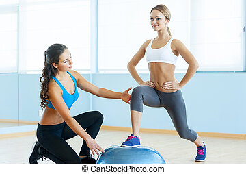 Exercising with fitness ball. Beautiful young woman in sports clothing exercising with personal trainer