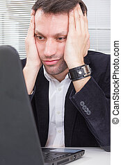 adult business man looking at screen laptop computer with a shocked upset expression, tired because of work