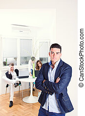 fashion man sulking standing in business atmosphere with colleagues behind him working as team