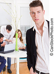 young modern fashion casual man in a business atmosphere with colleagues behind him