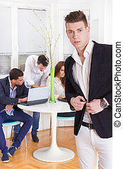 fashion man in a business atmosphere with colleagues behind him