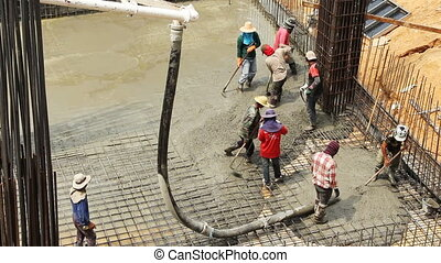 Workers pouring cement for construc