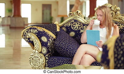 Beautiful woman using tablet in a hotel lobby - Beautiful...