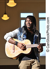 young man playing the guitar - young black man playing a...