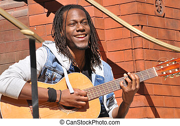happy young man playing guitar - positive young man playing...