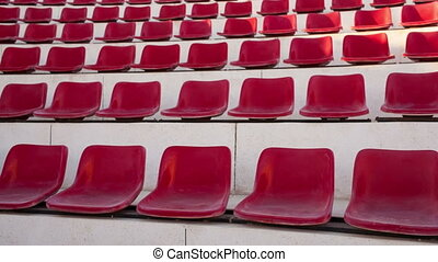 Outdoor seating - Tilt shot of rows of vacant red seats at...