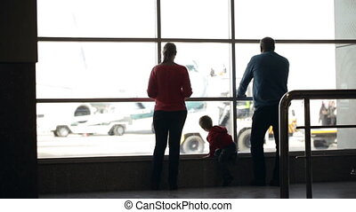 Young family watching planes at an airport