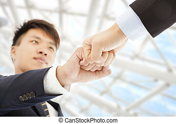 Two businessman fist  collide each other to celebrate