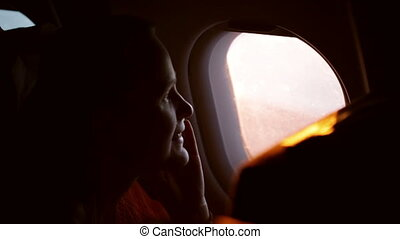 Woman talking on the phone in the plane