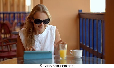 Woman in cafe with tablet PC - Dolly shot of young woman on...