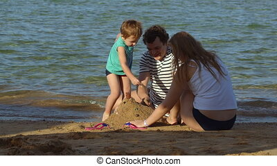 Family spending time by the sea - Young parents and their...