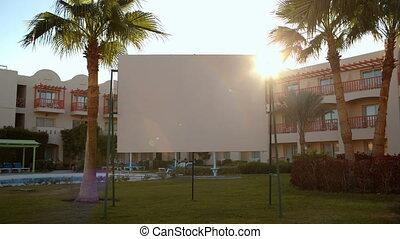Sun flare behind a blank urban billboard
