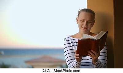 Woman reading a book - Young woman reading a book outdoor,...
