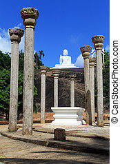 Columns and Buddha - Stone columns and white Buddha in...