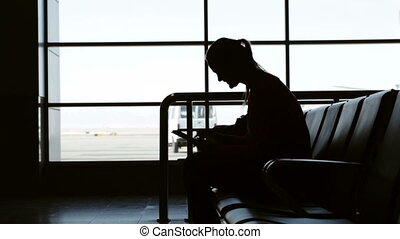 Buying airflight tickets online - Woman in the aiport lounge...