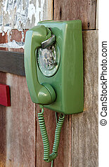 green retro telephone on wooden wall