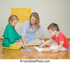 Woman plays with children at home.