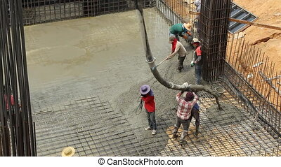 Workers pouring cement for construction