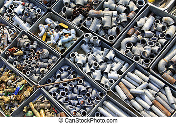 Metal plumbing pipe fittings piled up in the box in a market...