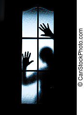 Scared boy behind glass door showing one hand