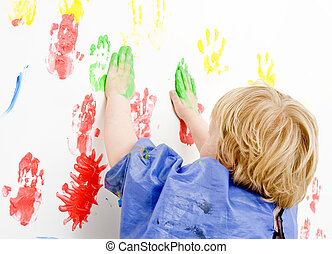 Finger paingint - Young boy finger painting on a wall