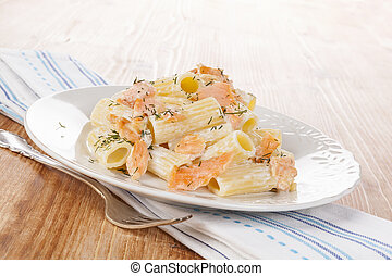 Salmon Pasta. - Penne pasta with salmon on white plate on...