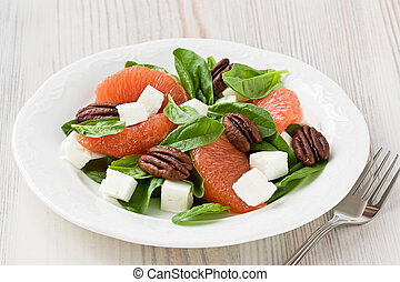 Spinach grapefruit goat cheese salad with pecan on white...