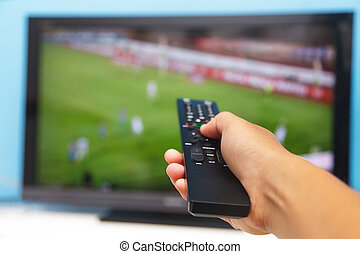 Hand pointing tv remote control towards the television as...