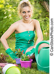 Beautiful woman planting flowers - Smiling young woman...