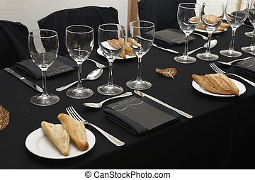 Black tablecloth with glasses and dishes. - Black tablecloth...