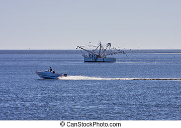 Boat Speeding Past Shrimp Boat - A shrimp boat being passed...