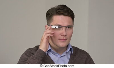 Skilled user - Man using smart glasses against grey...