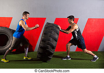 men flipping a tractor tire workout gym exercise - men...