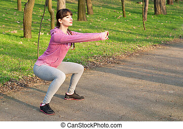 Squat exercises - Strong sporty woman doing squat exercises...