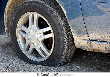 Flat Tire on Old Dirty Car - close up on the flat tire of a...