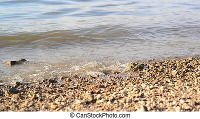 River bank with pebbles and waves of splashing water.