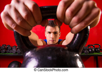 Kettlebell man portrait looking through the handle ring at...