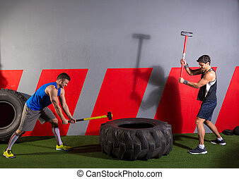 Sledgehammer Tire Hits men workout at gym with hammer and...