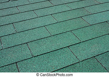 Green asphalt shingle in the shape of a rectangle on the...