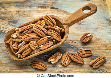 pecan nuts in a rustic scoop against a grunge wood...