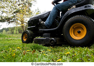 Lawn mower - Worker mowing with black riding lawn mower