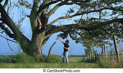 Climbing the tree - A woman supervising a boy who is...